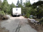 "In order to move my trailer onto my new land, I had to ""designate a driveway"" according to the county. So I worked really hard with a shovel, a pick axe and a tiny rented tractor to build a 50-foot driveway in only two weeks. I added a truckload of gravel, tamped it down, and then a neighbor used his truck to back my trailer onto my new pad."